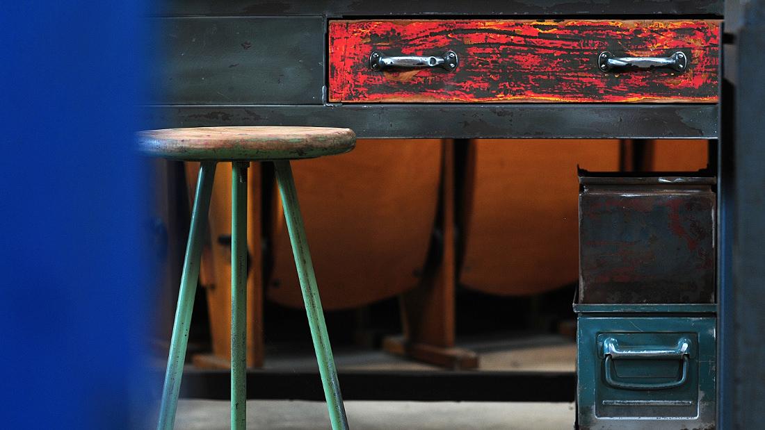 Kim Stobernack schenkt industriellen Originalen neues Leben: Liebevoll aufgearbeitete Werkbank mit einer roten Schublade und einem Industriehocker als Eyecatcher