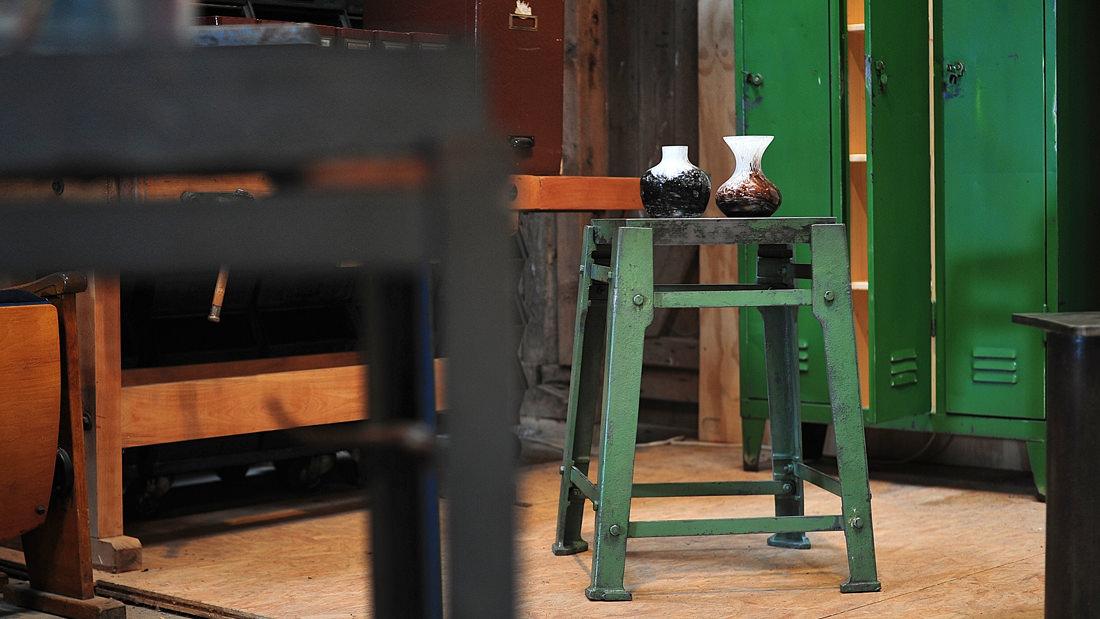 Auf einem kleinen Industrietisch werden Vintage-Vasen schön in Szene gesetzt