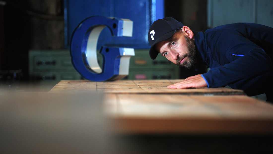 Designer Kim Stobernack testet die Oberflächenqualität eines Vintage Industrietisches
