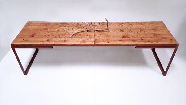 Dieser Tisch aus einer alten Schmiede hat Tischbeine und zwei schubladen aus rotem Metall